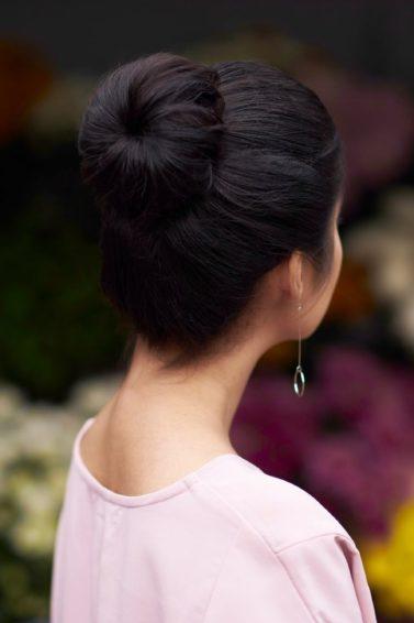 Wanita asia dengan model rambut cepol hitam menggunakan sock bun, warna rambut hitam
