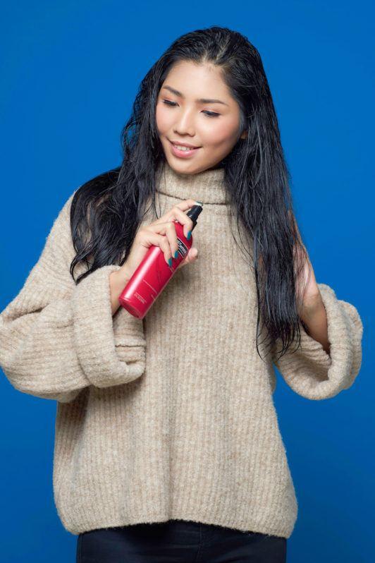 Wanita asia dengan rambut panjang hitam menyemprotkan heat protection spray – cara mengatasi rambut kusut