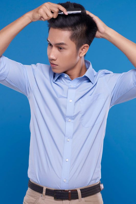 Pria asia dengan warna rambut hitam sedang menata rambut dengan sisir – tutorial menata gaya rambut pompadour