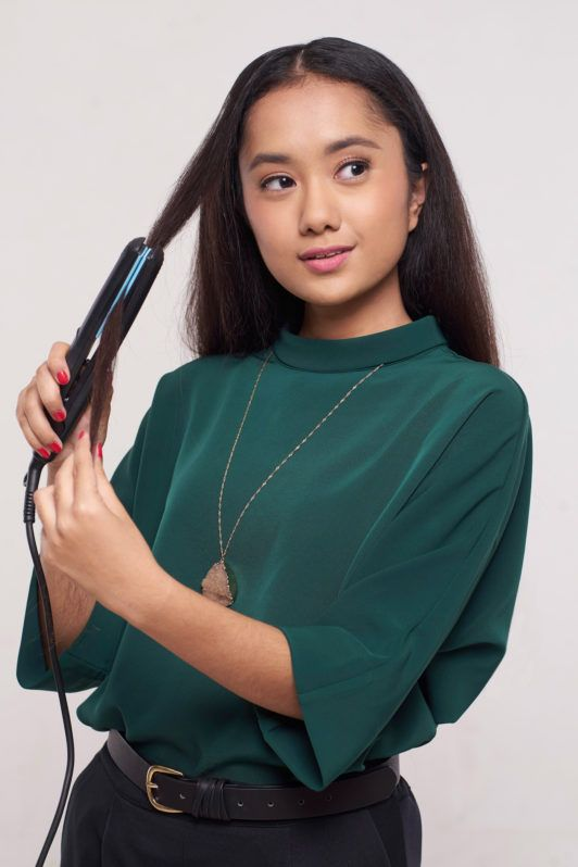 Wanita asia dengan rambut keriting panjang warna hitam menggunakan flat iron – cara mengeriting