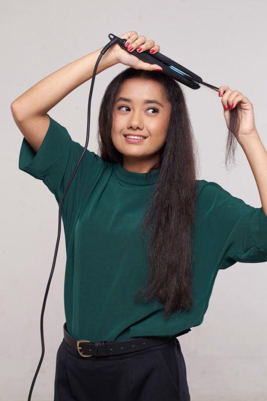 Wanita asia dengan rambut keriting panjang warna hitam mencatok sisa rambut dengan flat iron.