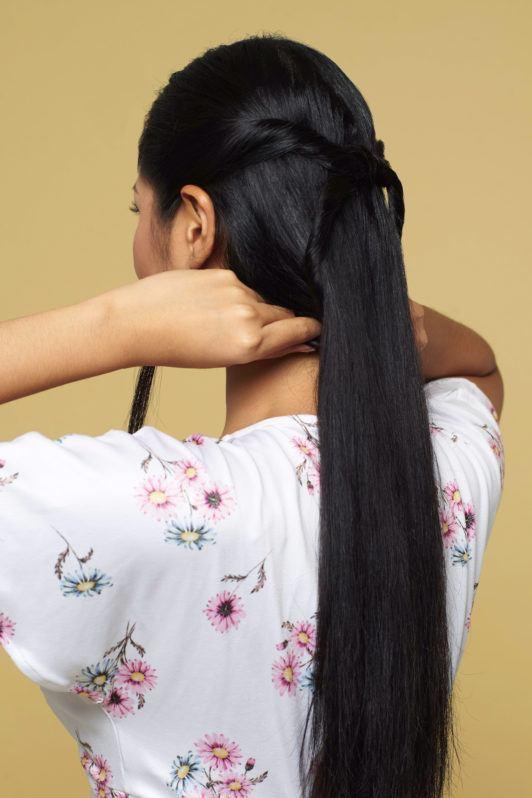 Wanita asia dengan rambut hitam panjang menata rambut dengan gaya knotted bubble ponytail