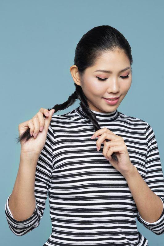 Wanita asia dengan rambut hitam membuat rambut double rope braid ponytail