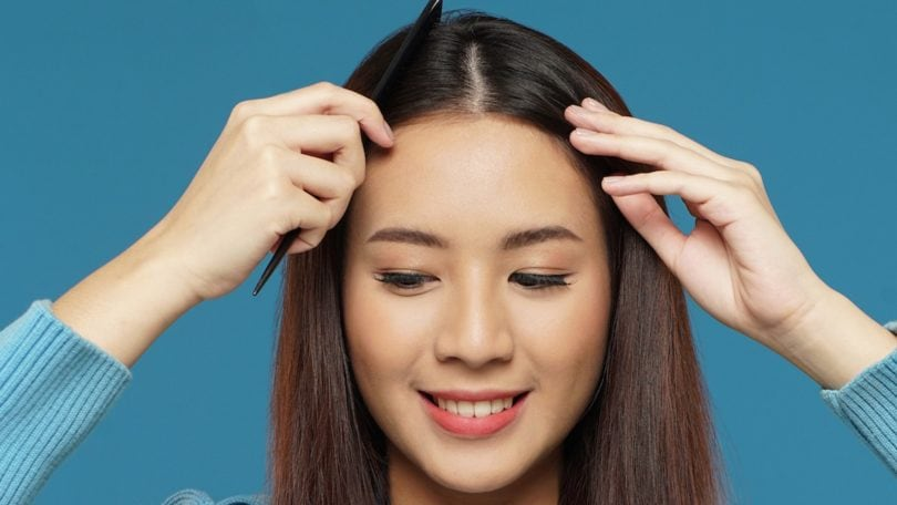 Wanita asia dengan rambut cokelat panjang membagi rambut menjadi dua