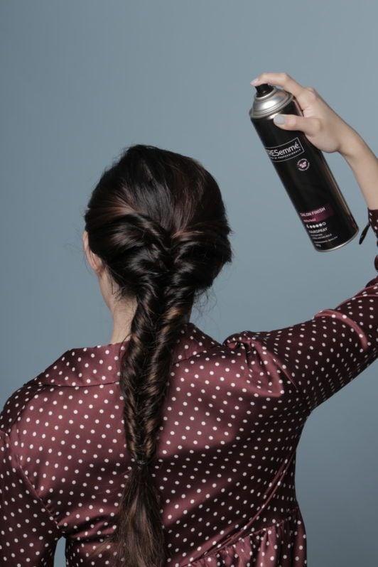 Wanita asia dengan rambut cokelat menyemprotkan hairspray ke rambut - bohemian faux braid
