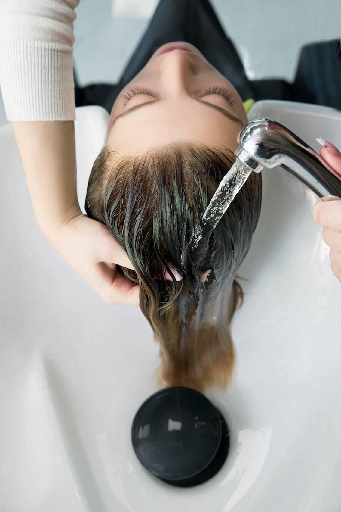 Wanita kaukasia dengan warna rambut cokelat kehijauan keramas dengan air mengalir