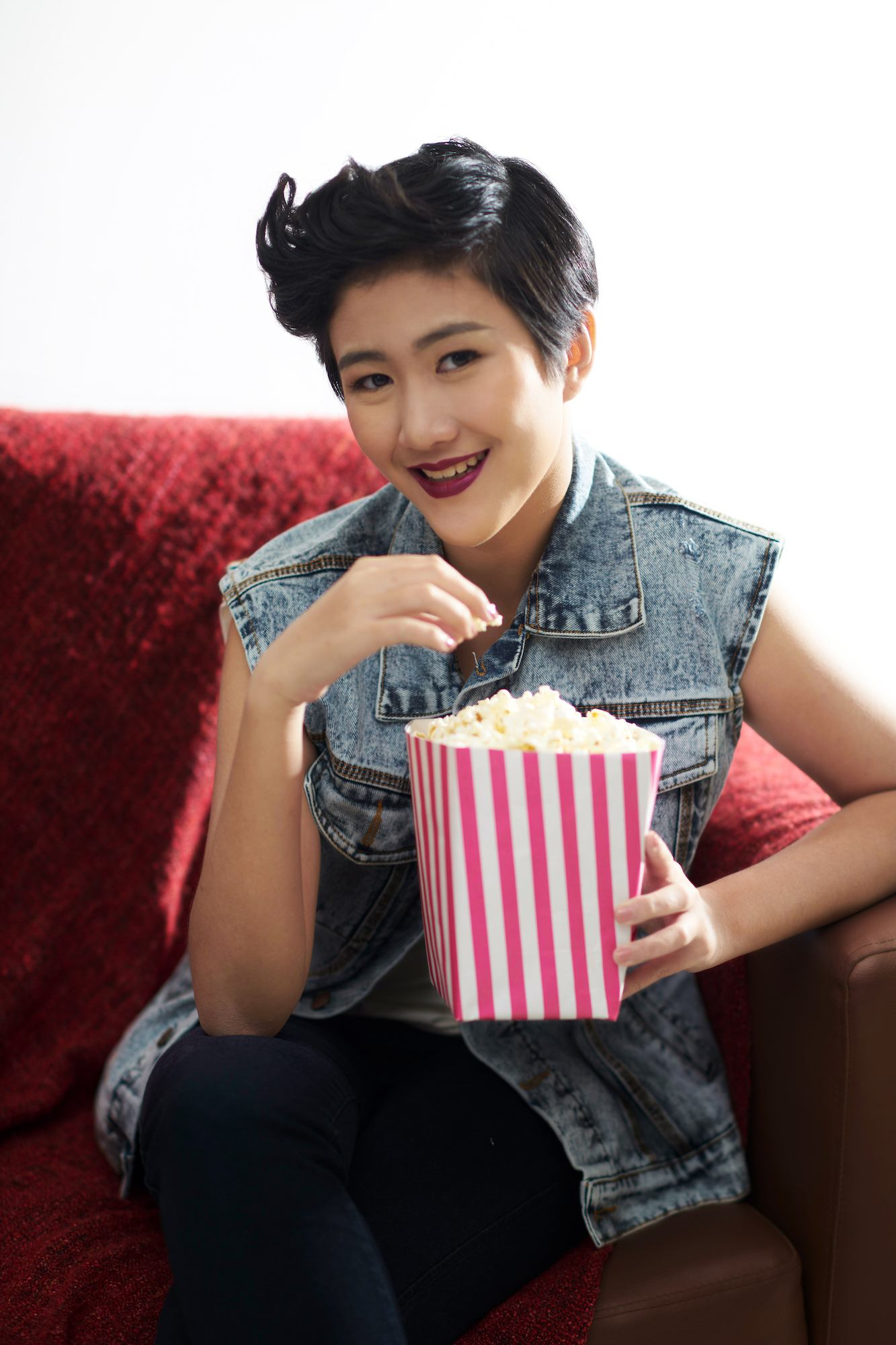 Wanita asia dengan gaya rambut long pixie cuts sedang menyantap popcorn.