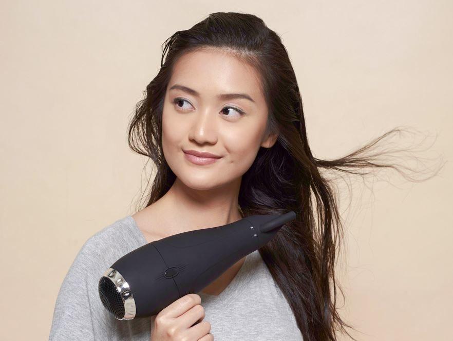 perempuan asia memakai hair dryer untuk mengeringkan rambut panjang