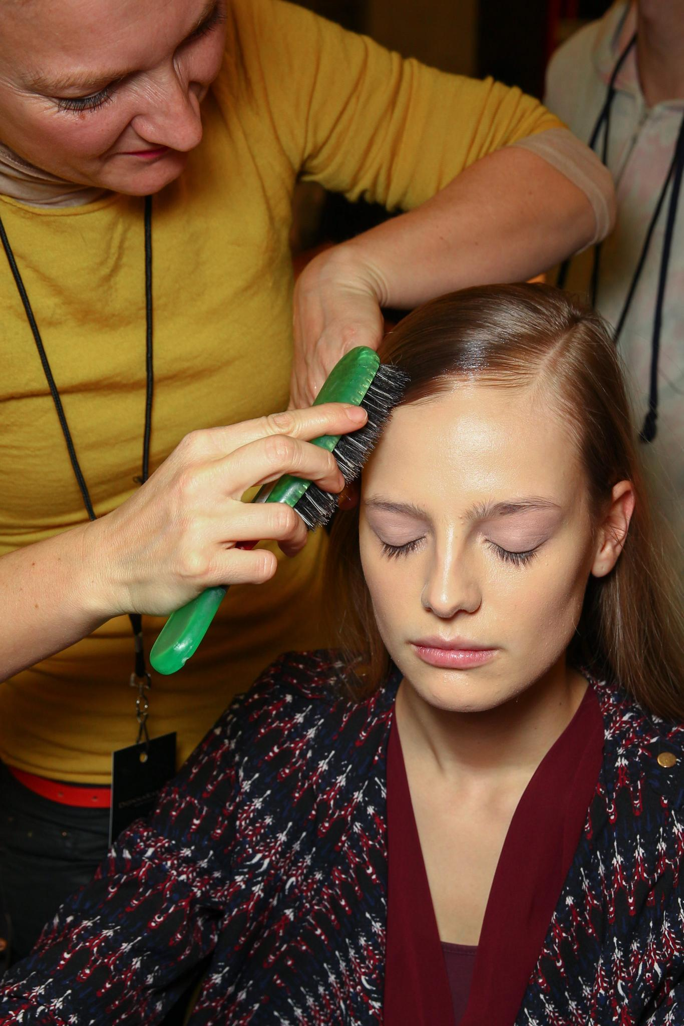 mujer peinando el pelo a modelo en backstage