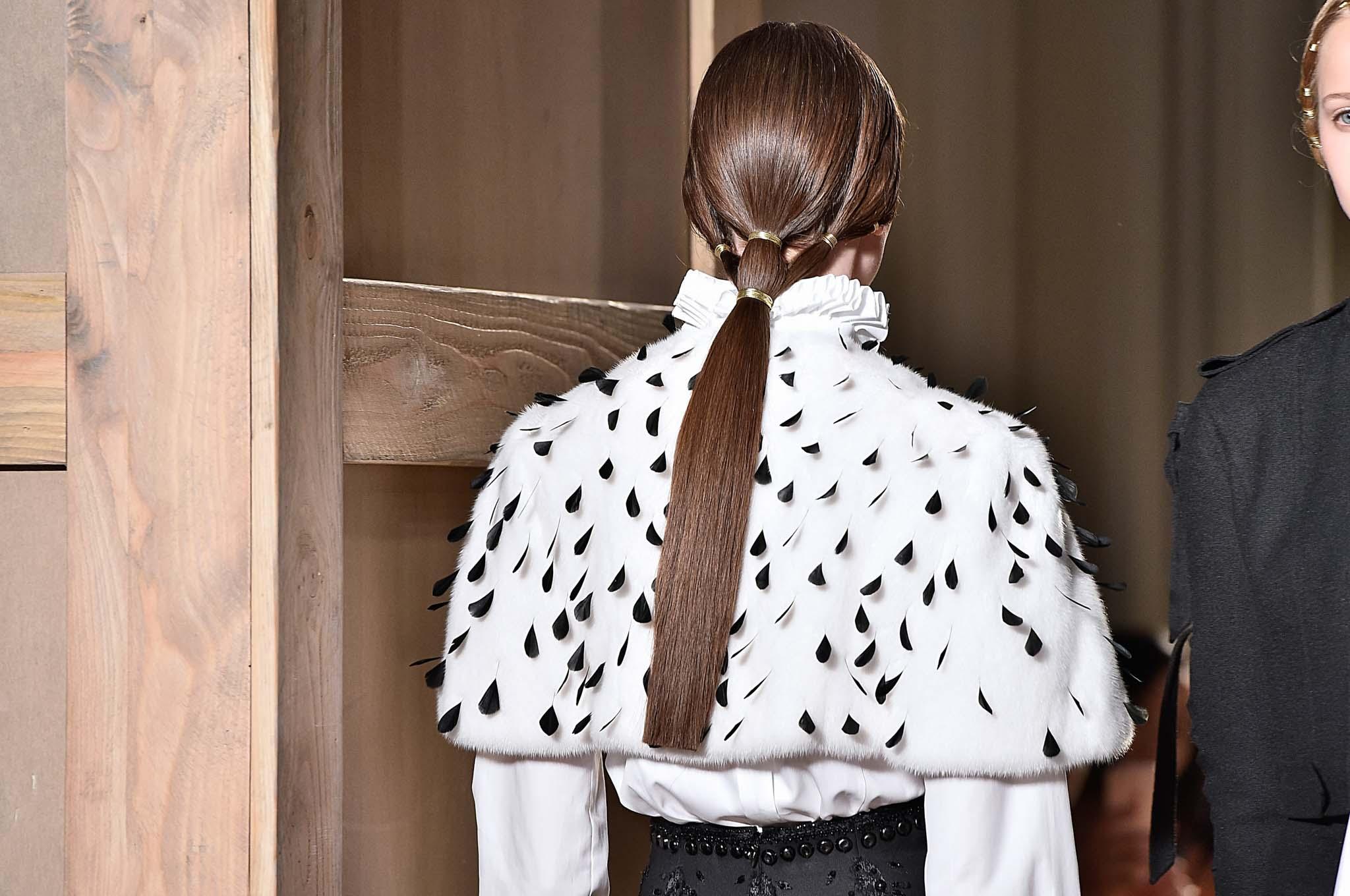 Vista desde atrás de melena castaña atada con una coleta sofisticada (que sale de tres mechones)