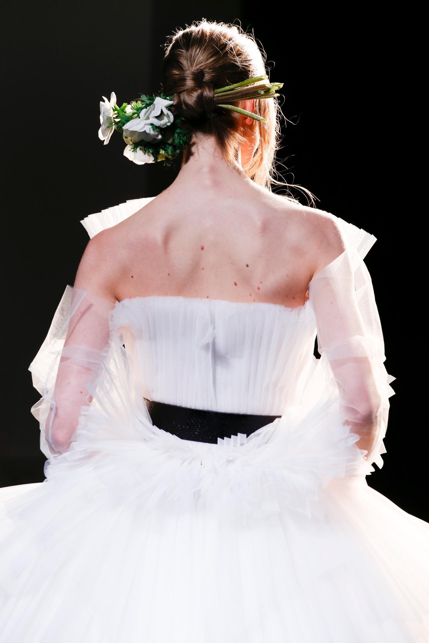 Mujer de espaldas, con pelo atado y un tocado floral