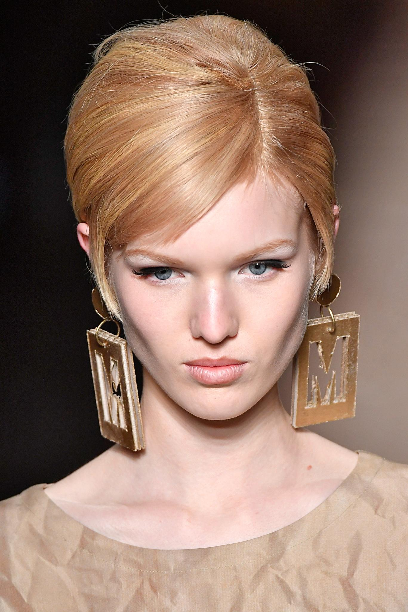 Peinado recogido, melena rubia raya al costado y grandes aros dorados