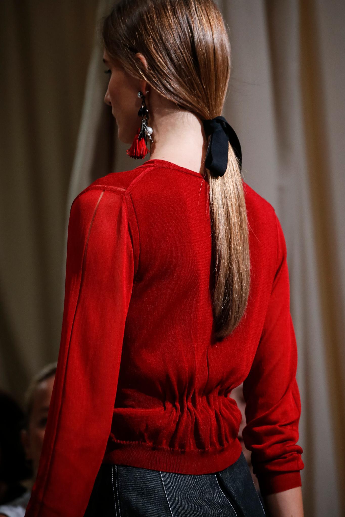 Mujer vista desde atrás, cabellera lacia, rubia con coleta baja atada con un lazo negro