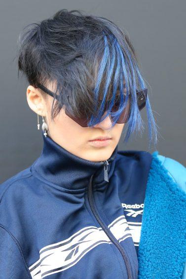 Mujer de cabello corto, castaño oscuro, con mechones en azul. Lleva gafas de sol