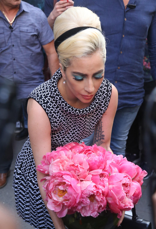 Mujer rubia con el cabello recogido en un batido alto y bincha negra