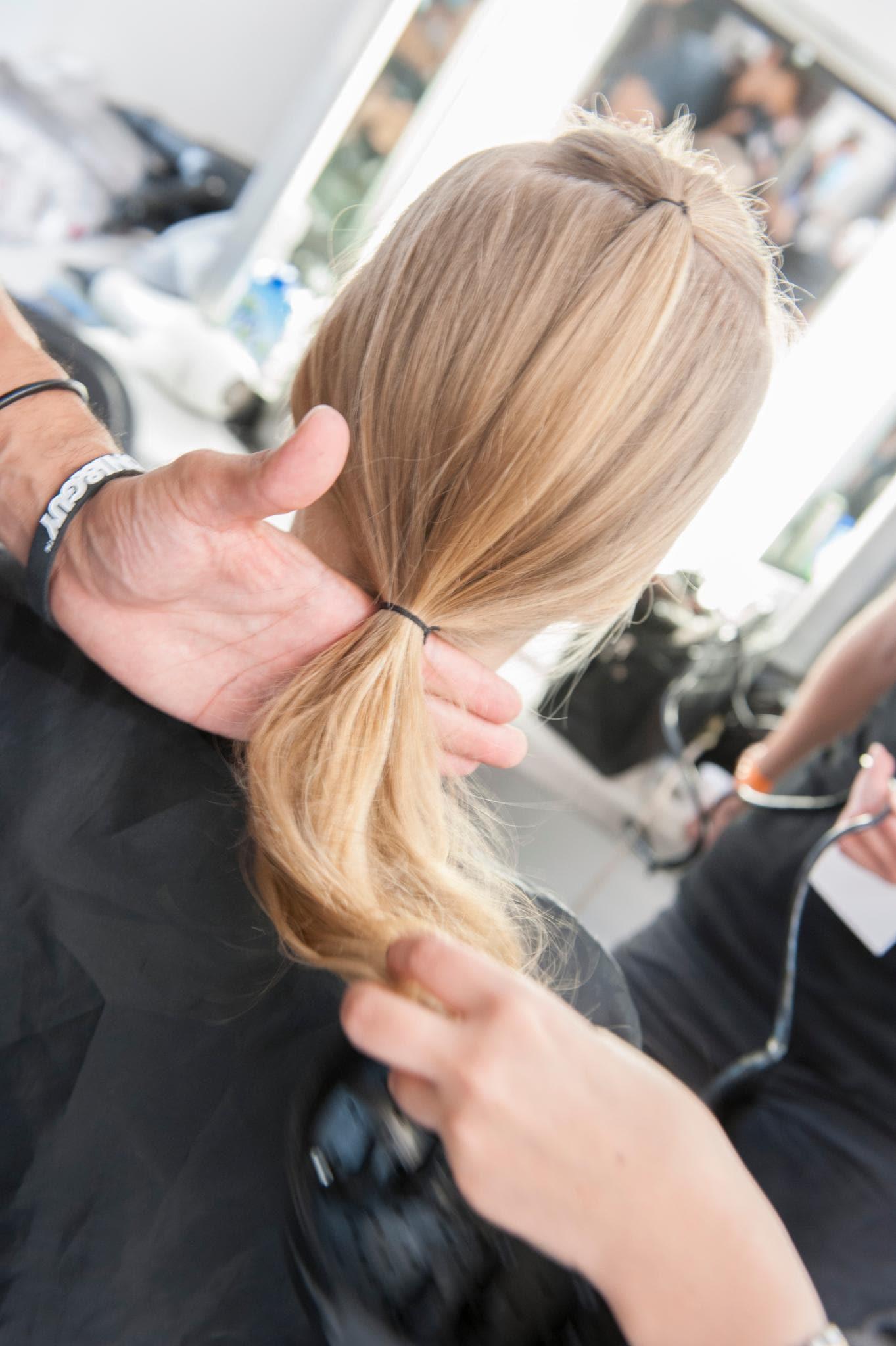 Backstage de un peinado, cabellera rubia atada con dos gomitas negras