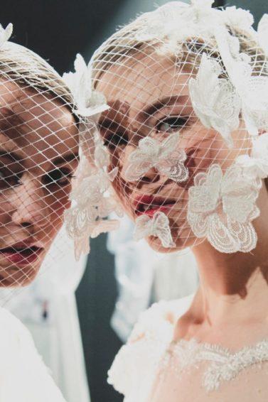 Dos mujeres con tocados blancos y una redecilla blanca a modo de velo que les cubre el rostro