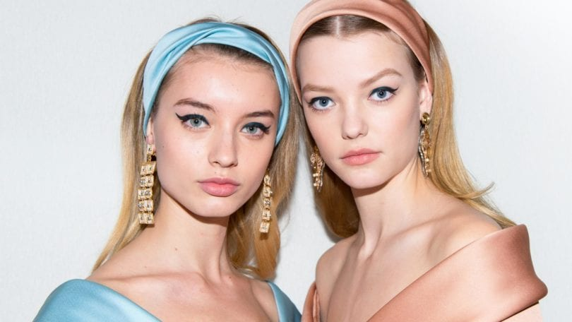 Dos mujeres rubias de cabello suelto a la altura de los hombros, ambas llevan vinchas gruesas de tela