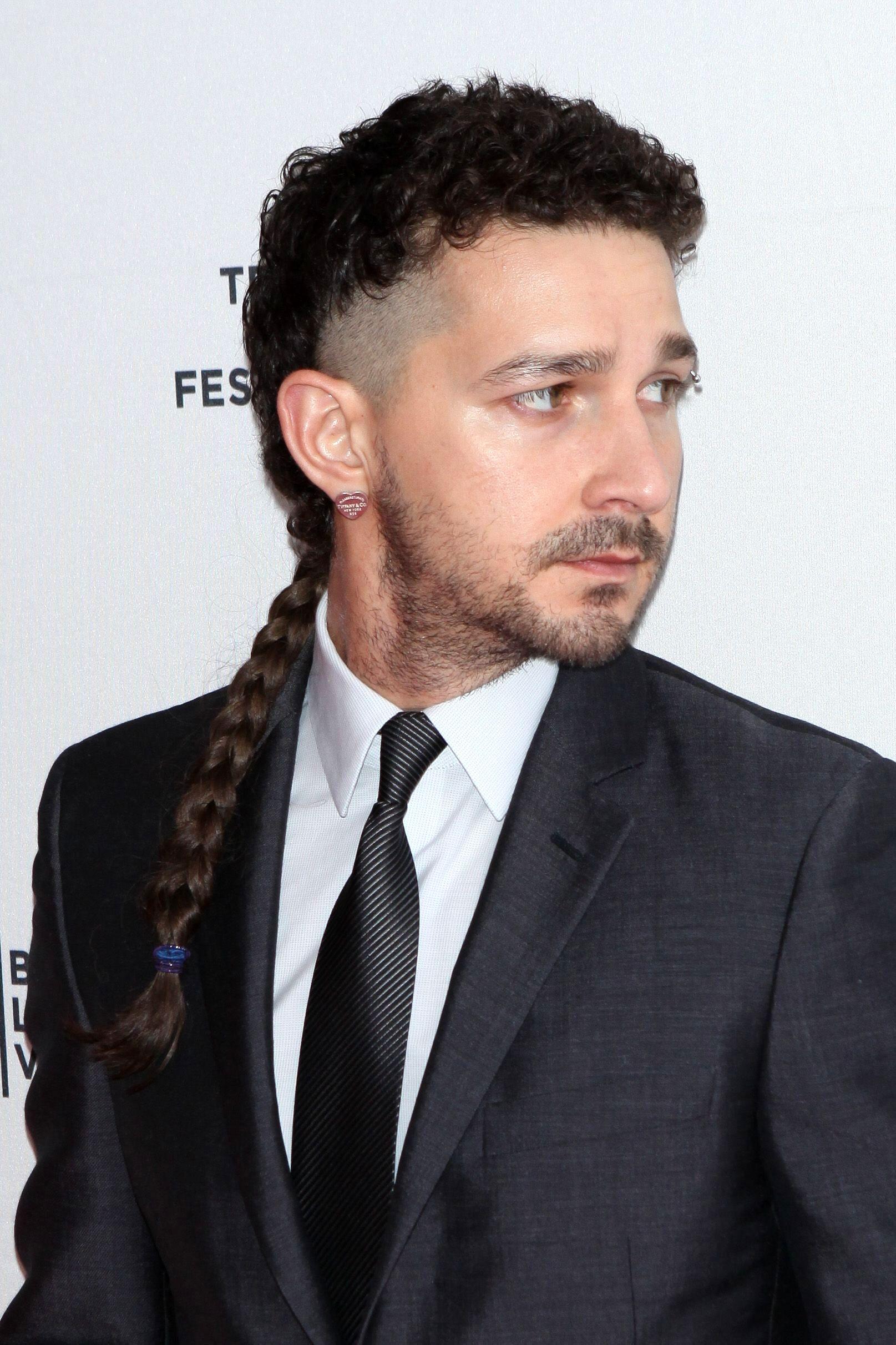 Hombre de cabello largo, corto en la base, rapado hacia los costados y con trenza