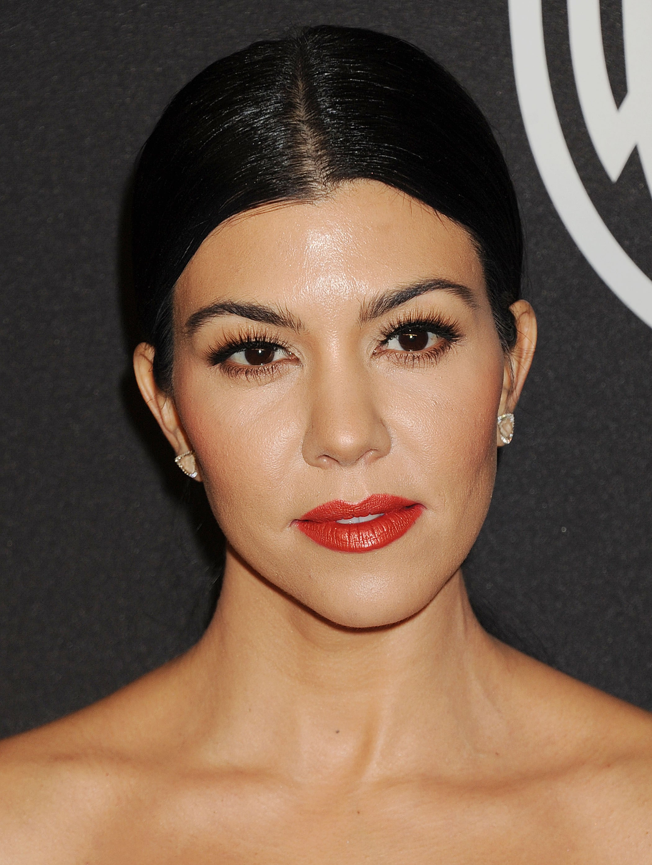 Kourtney Kardashian con cabello atado hacia atrás y raya al medio