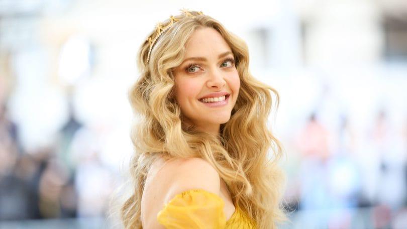 Mujer rubia de cabello bien ondulado, largo, con raya al medio y corona dorada
