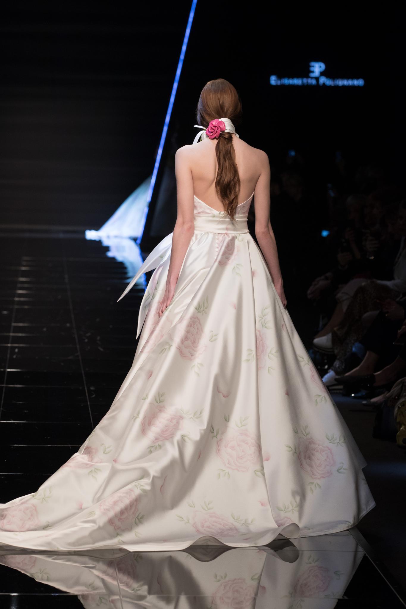 Vista de atrás de mujer castaña peinada con una coleta sostenida por un aplique blanco y rosa