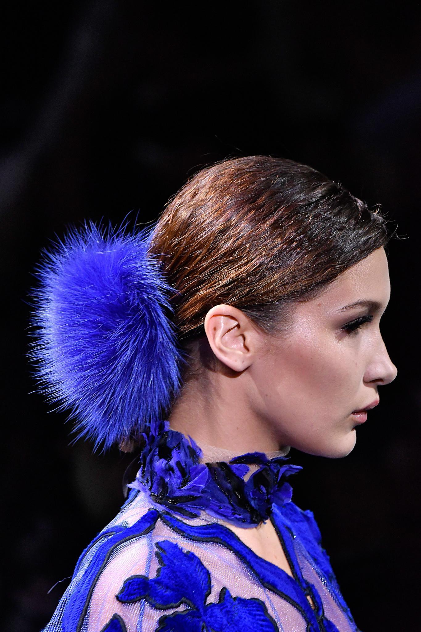Toma de perfil, de mujer con cabello recogido con un gran pompón azul