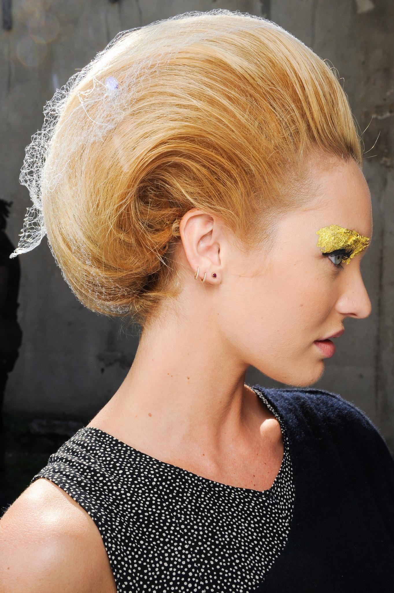Vista de perfil de cabello rubio anaranjado peinado hacia atrás con mucho volumen