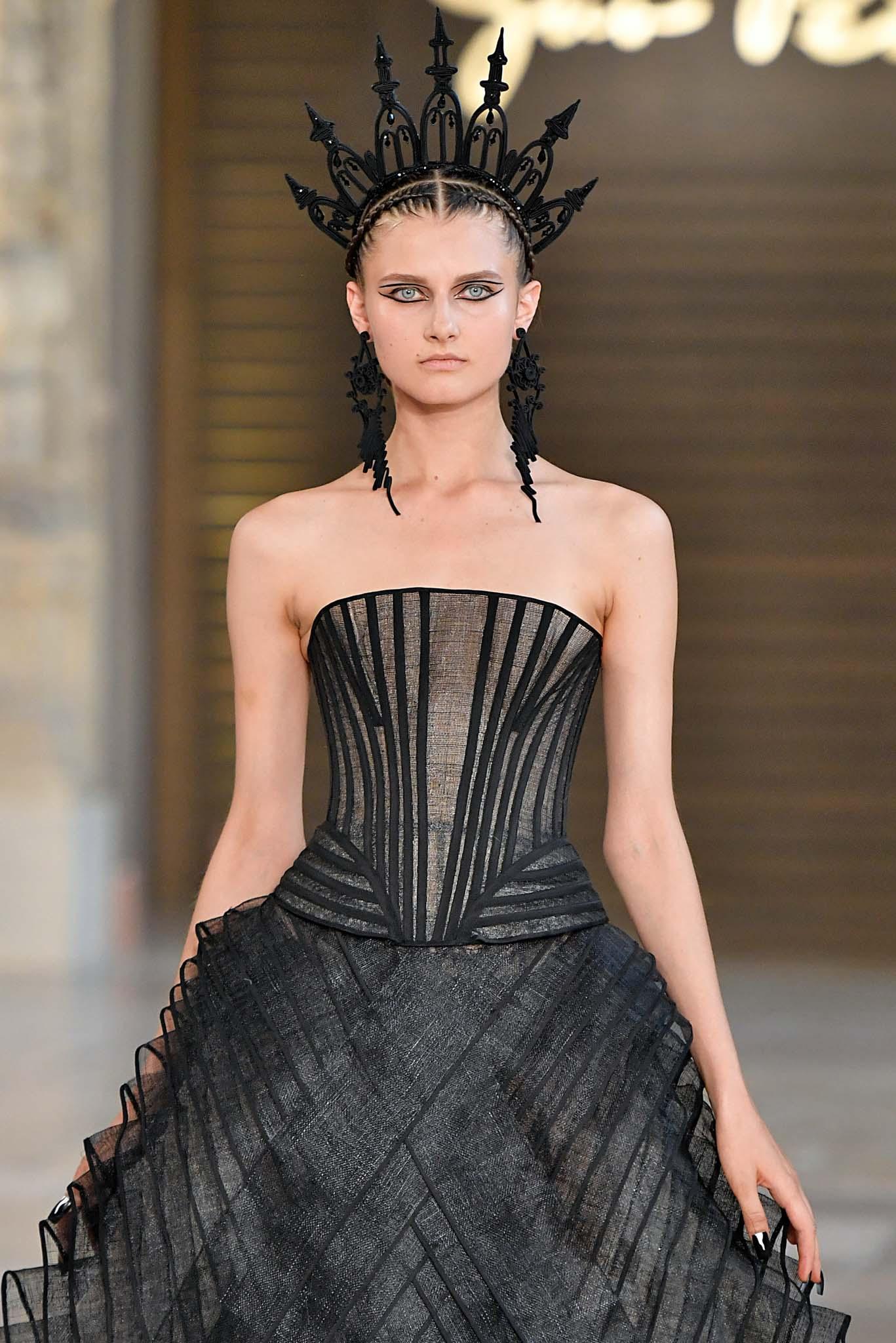 Mujer de cabello castaño oscuro, el cual casi no se ve porque está cubierto por un aplique/adorno inmenso color negro