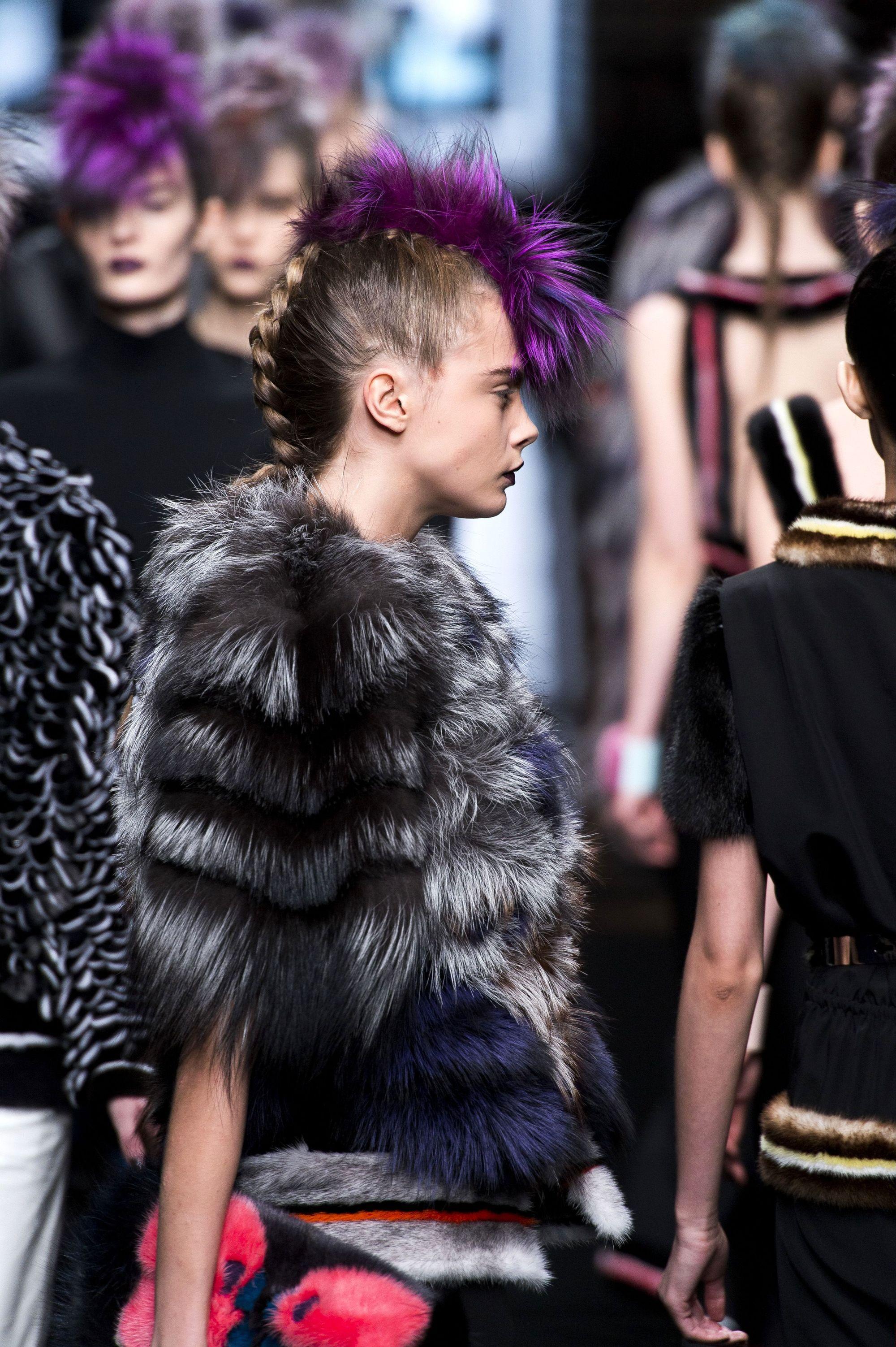 Vista de perfil de mujer castaña peinada con una trenza al medio que le zurca la cabeza y una cresta violeta encima.