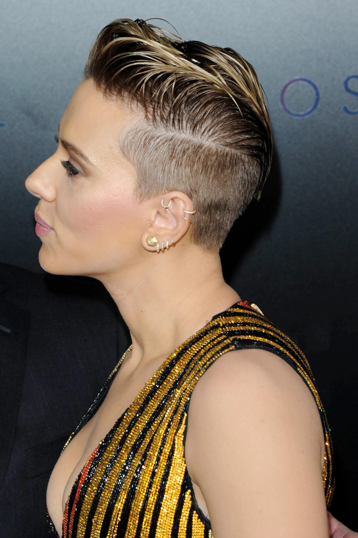 Mujer castaña con reflejos rubios, lleva el cabello peinado hacia atrás con gel y rapado a los costados