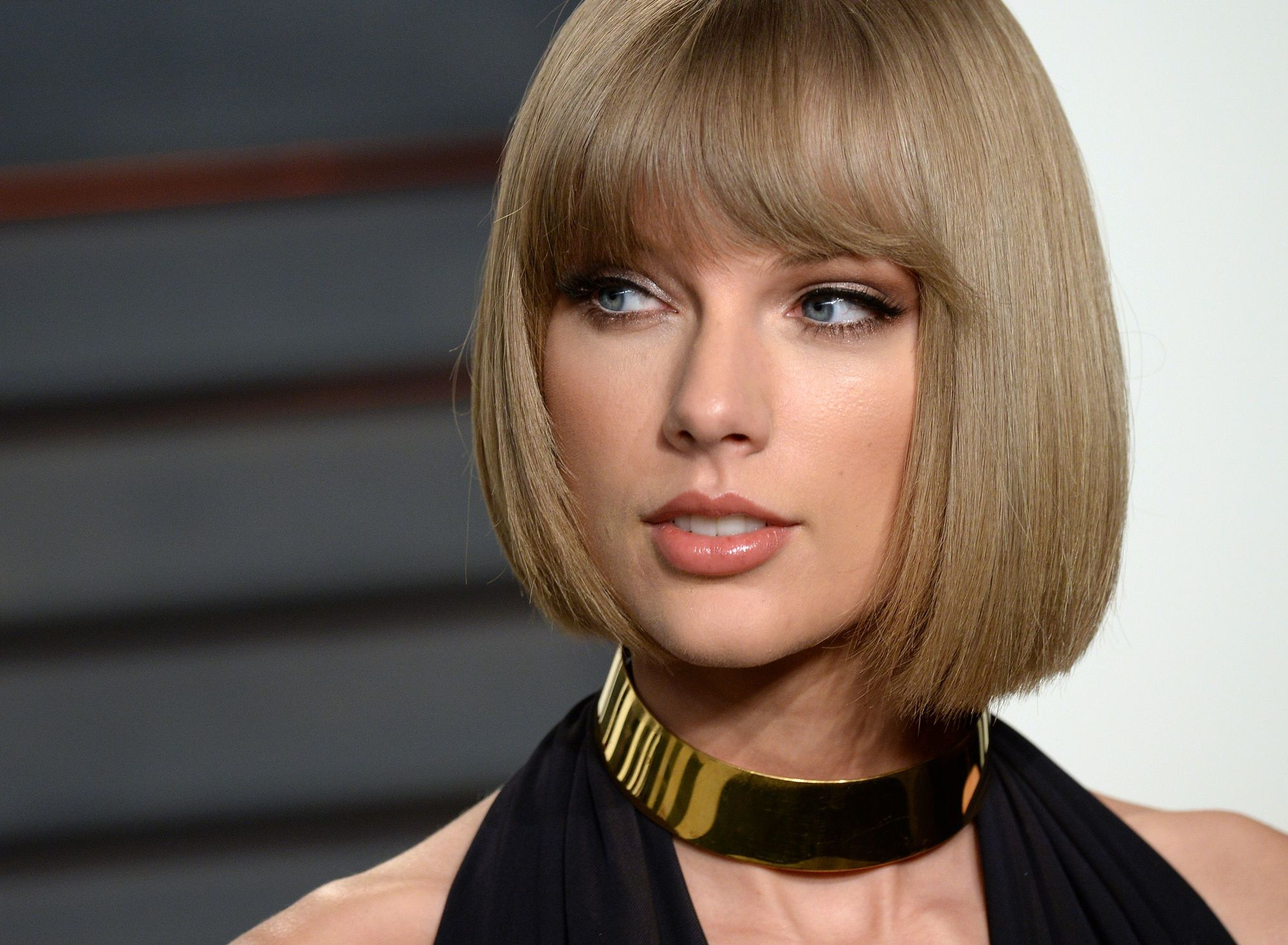 Taylor Swift con cabello rubio ceniza, super planchado. Corte carre peinado hacia adentro con flequillo