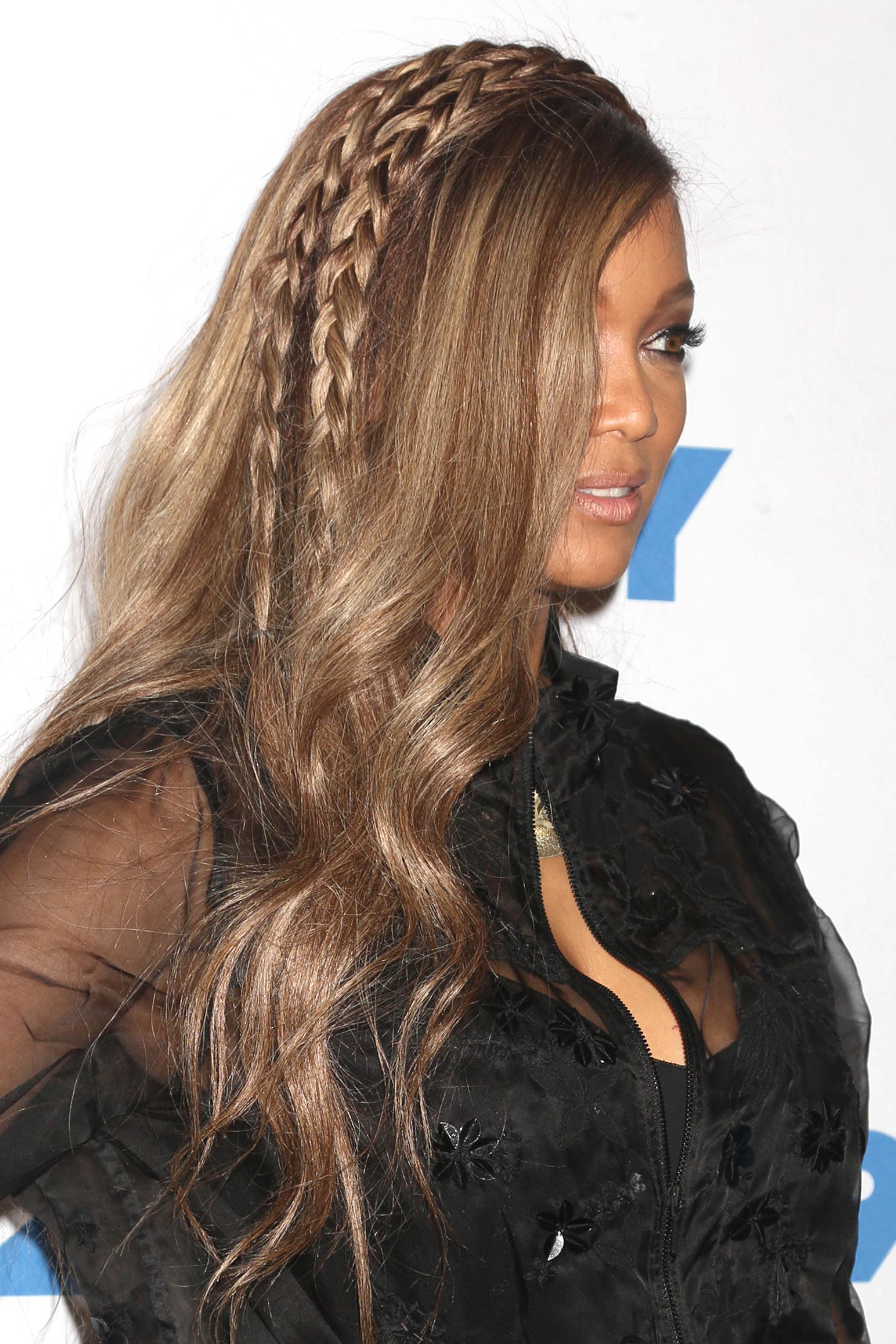 Mujer de melena castaña, lacia, con movimiento y raya al costado. Lleva dos trenzas entre el medio del cabello