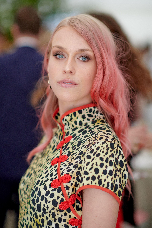 Mujer de melena lacia, con ondas, lleva el cabello rubio con puntas rosas y raya al costado