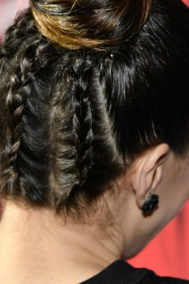 Primer plano de cabello castaño oscuro recogido con trenzas cosidas