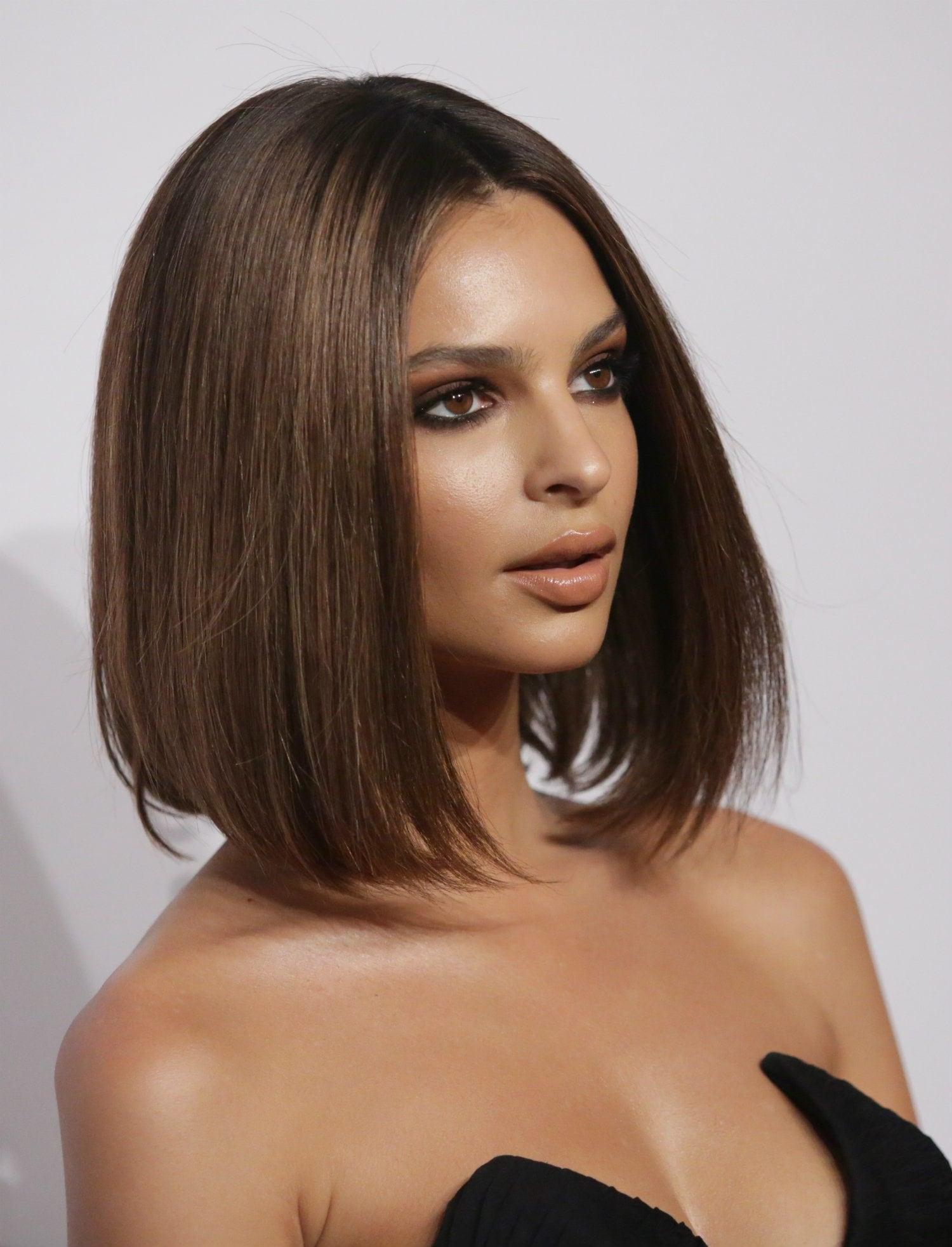 Mujer castaña con melena tipo carre, el pelo es lacio y lo lleva con raya al medio