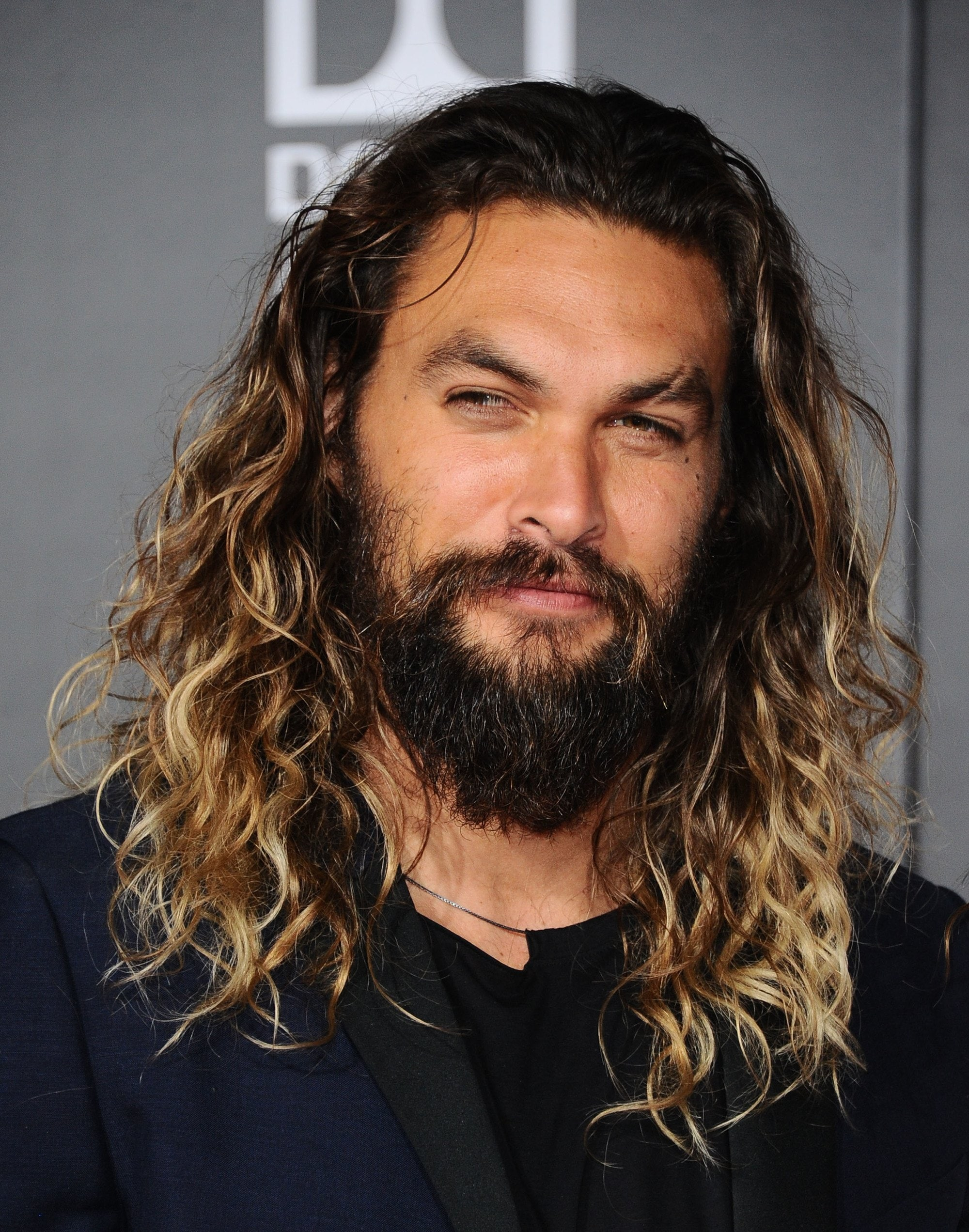 Hombre de raices castaño oscuro y pelo largo con rulos color rubio. Tiene barba y bigotes