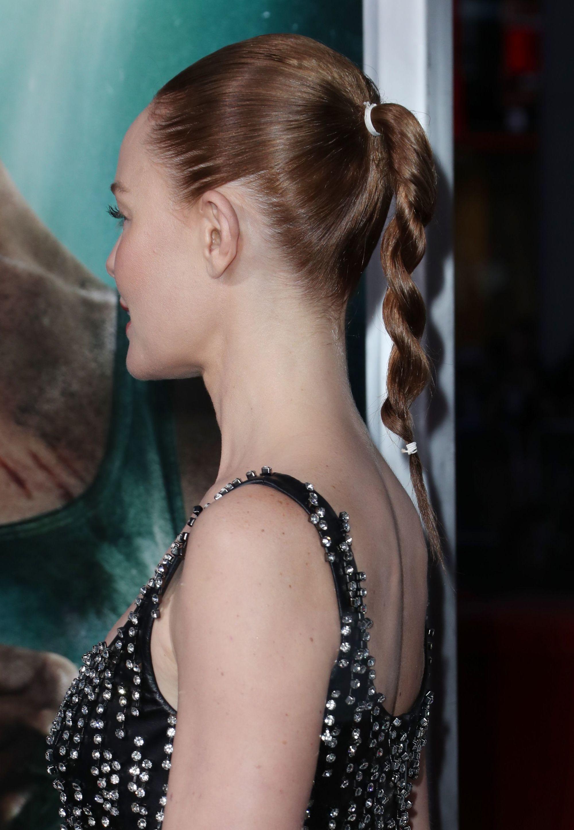 Vista de perfil de mujer pelirroja con cabello peinado hacia atrás y una especie de trenza