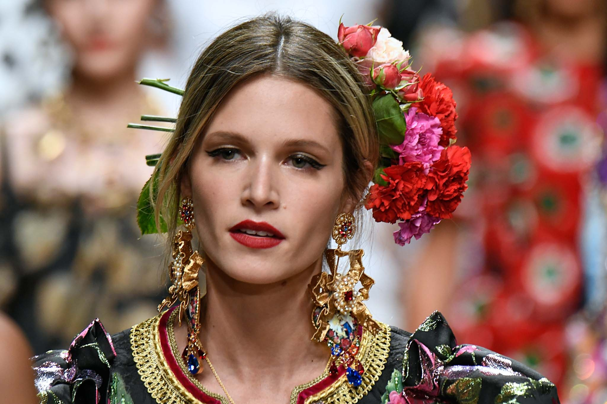 Mujer rubia de melena atada con raya al medio, lleva una gran corona de flores naturales a un costado del cabello