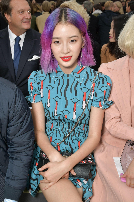 Mujer oriental con corte carre, raya al medio y cabello en colores fuscias violaceos