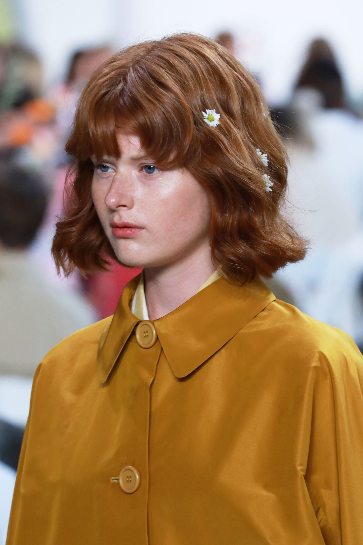 Mujer colorada con corte a la altura de la quijada, lleva el flequillo bien tupido y unas margaritas en la cabellera