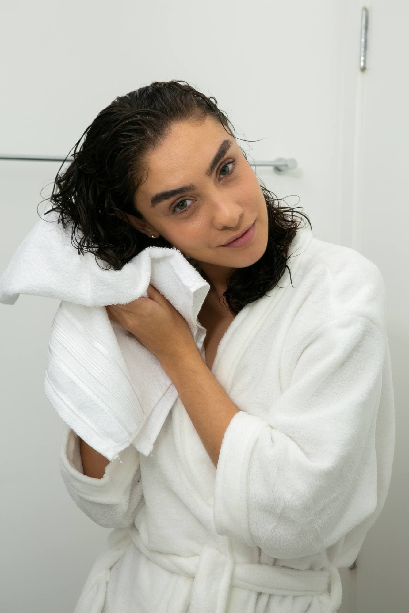 modelo de cabelo cacheado secando os fios com uma toalha