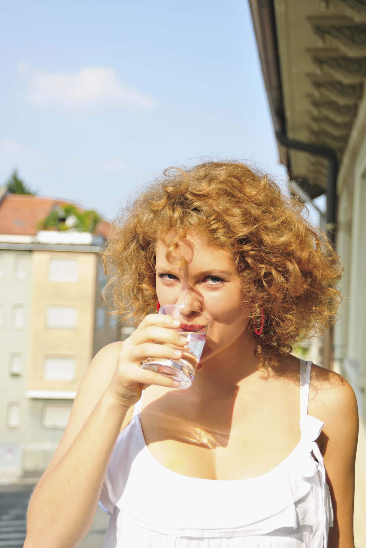 Modelo de cabelo loiro, cacheado, corteshort bob, bebendo água