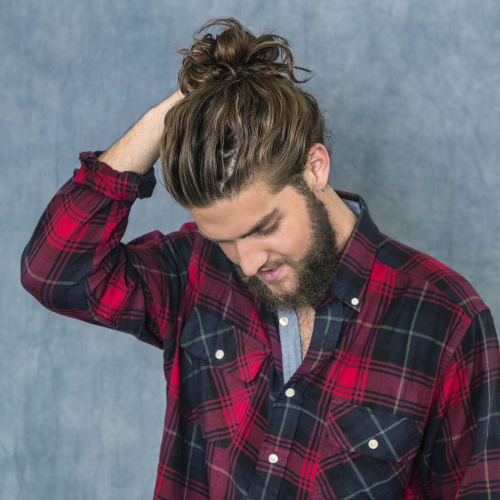 Modelo com Produtos para cabelo masculino óleos de tratamento e coque masculino