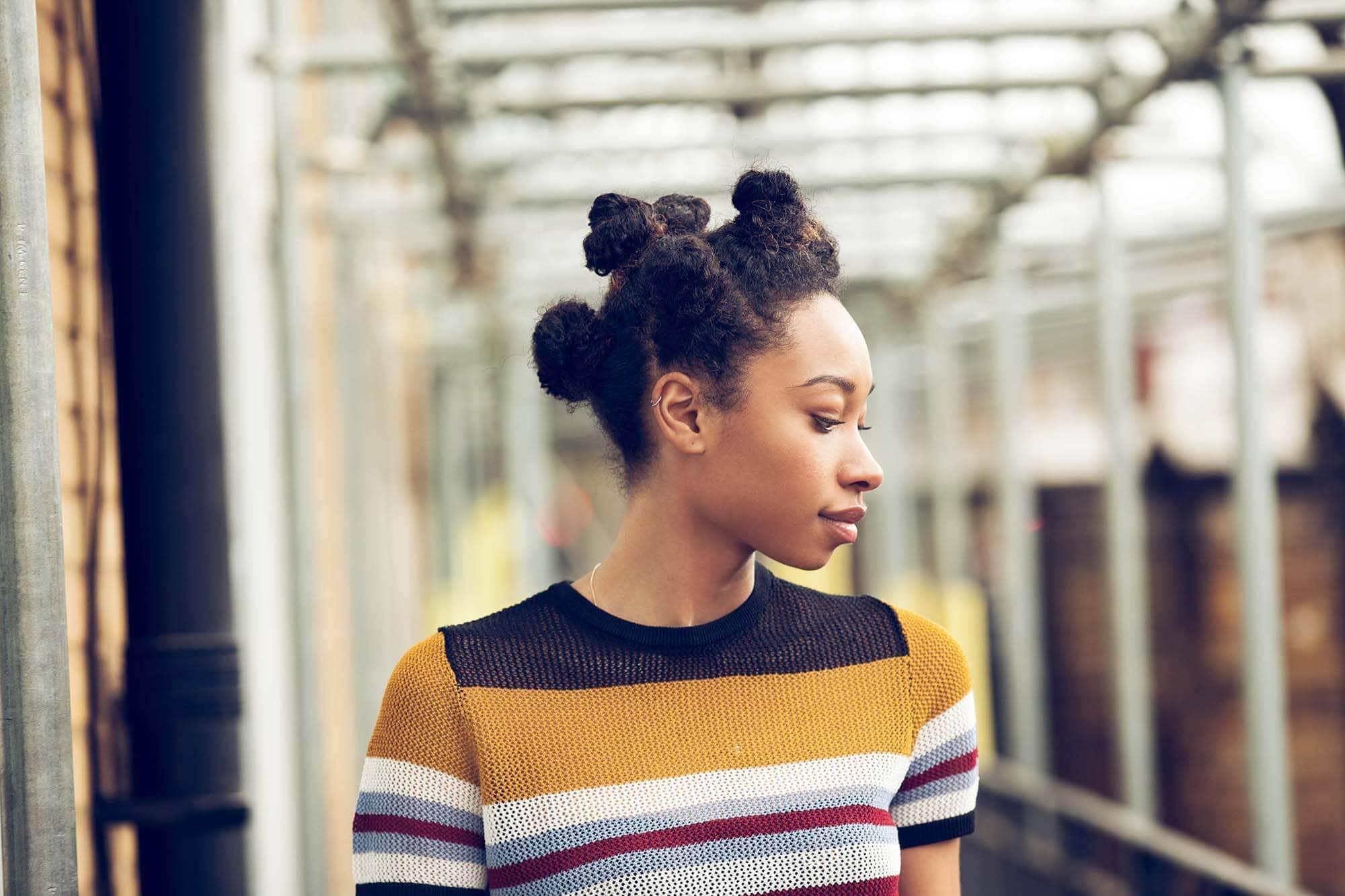 Mulher usa bantu knots como um dos penteados afro sugeridos
