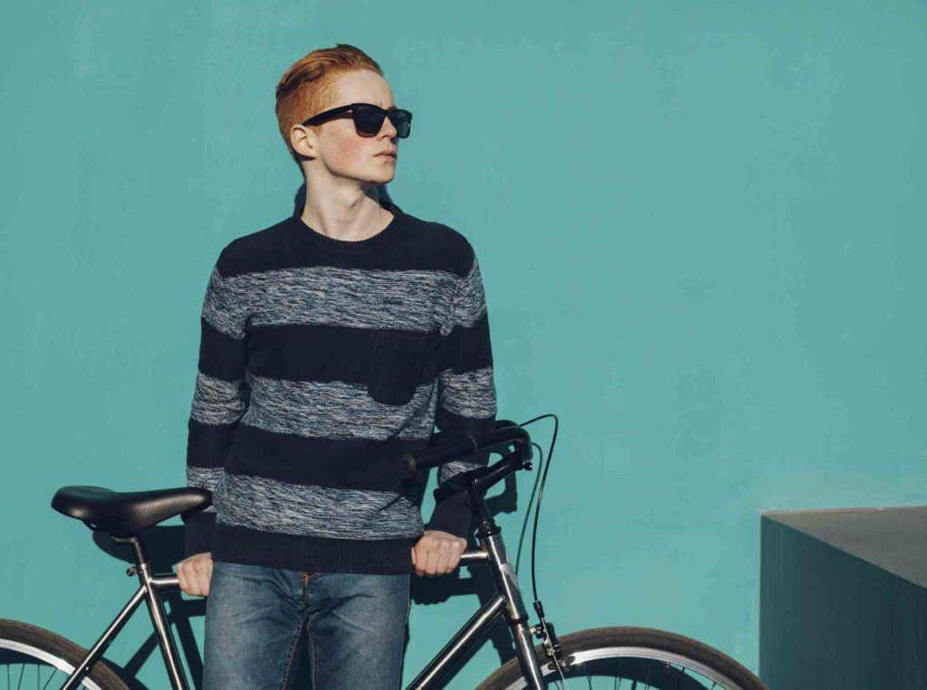 Homem com cabelo natural ruivo ao lado de sua bicicleta