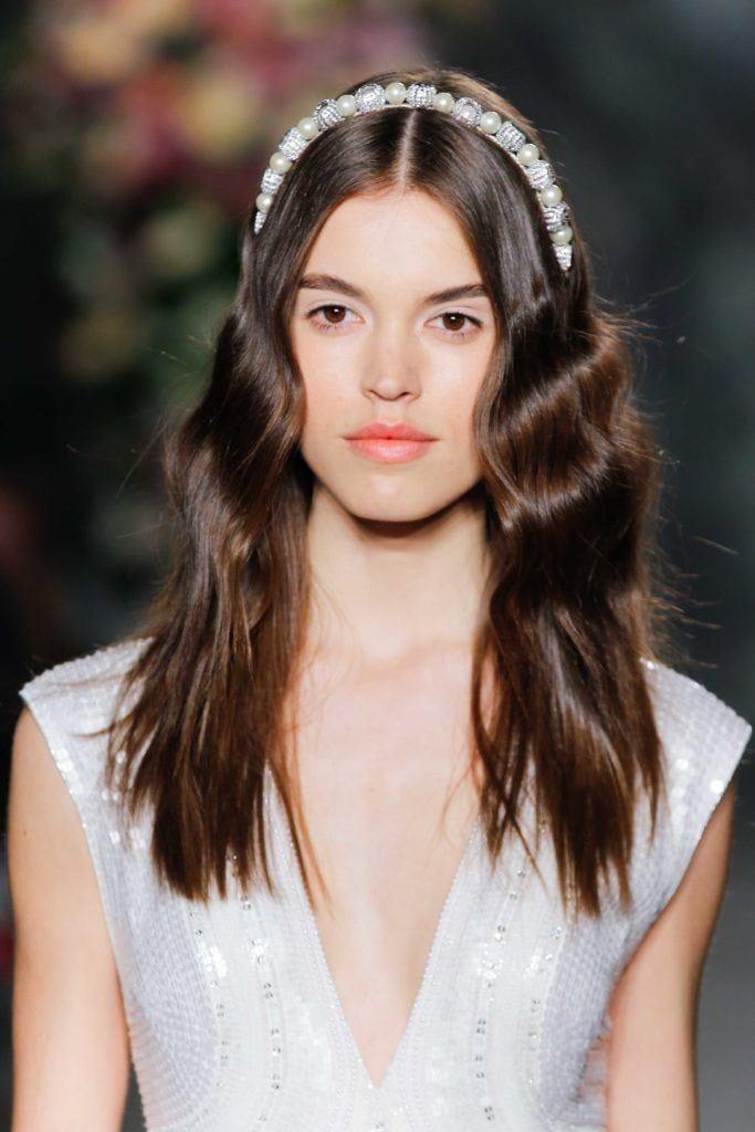 Modelo desfila com vestido branco e chapinha marcada nos fios castanhos, uma das ideias dos ondulados para testar