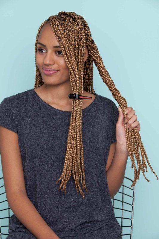 Mulher negra usa camiseta escura e ensina como fazer uma franja com nó duplo em cabelo trançado