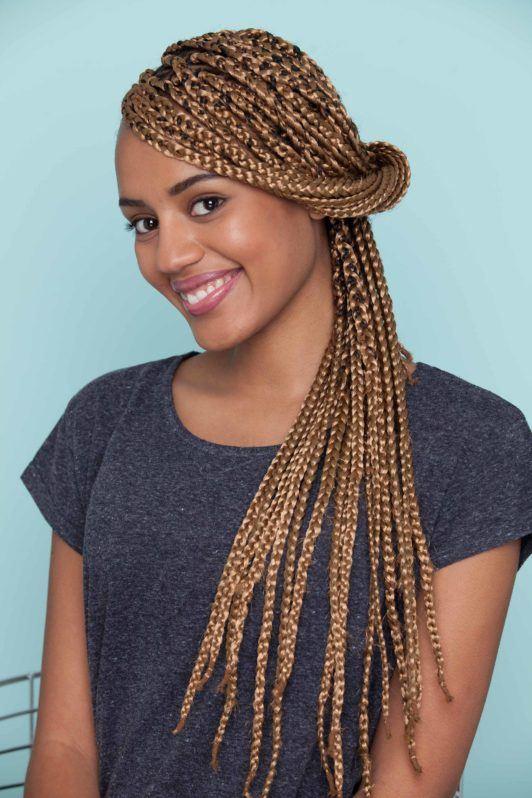 Mulher negra usa bluza azul escura e mostra o resultado do penteado, depois de ensinar como fazer uma franja com nó duplo em cabelo trançado