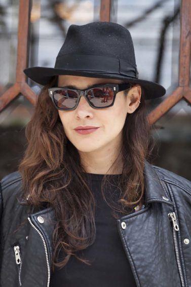 Mulher com cabelo ondulado castanho usa chapéu e roupa preta. Ela ilustra matéria sobre Detox de secador de cabelo